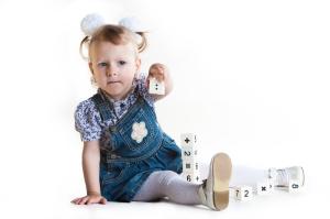 little girl plays cubes